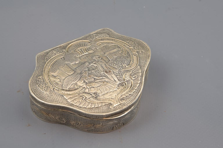 With hallmarks. Three-lobed flat-top box made of silver in its color decorated on the edge and lid with elements on chopped luster. The upper part presents a scene framed by scallops and elements reminiscent of Rococo, starring a couple located in