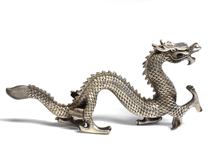 This model of dragon is a fine example of animal sculptures in the late Qing dynasty style. The four-clawed dragon has one front talon in pursuit of its subject, likely a flaming pearl, while the other three are firmly planted on the ground. The