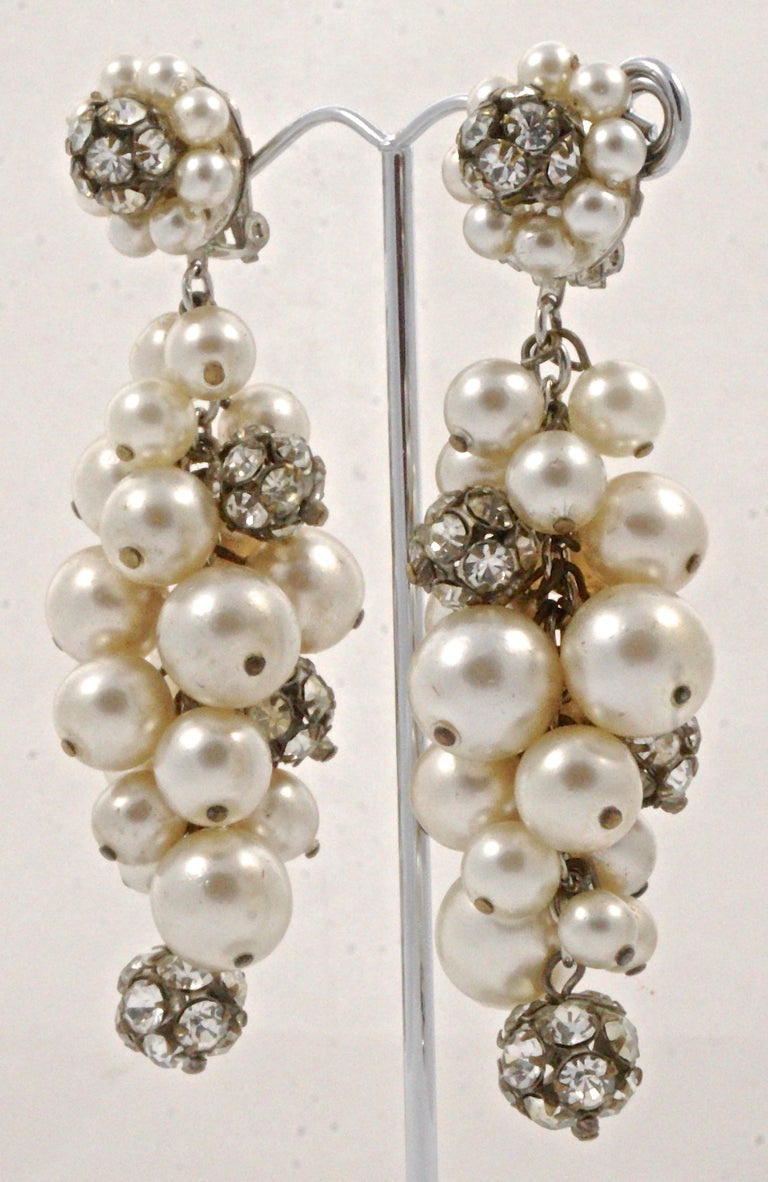 Glamorous vintage silver tone and bronze tone clip on drop earrings, featuring clusters of cream faux pearls and rhinestone balls. Measuring length 8.5cm / 3.34 inches, circa 1960s. The clips work well, there is wear to the silver plating, and some