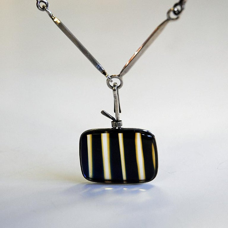 A very beautiful vintage Bengt Liljedahl rod chain necklace with a fantastic clear, yellow and black striped mounted glass pendant decorated with smaller yellow stripes between and then surrounded by a thin silverframe. A really beautiful piece of