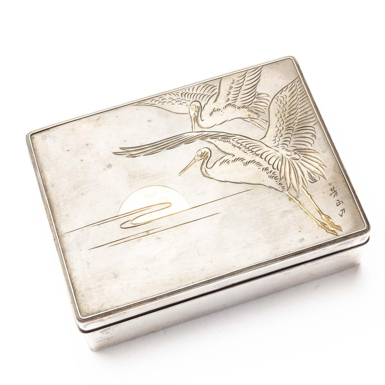 An elegant silver cigarette box from Japan, with a wooden lacquered interior. It has a delicately engraved bronze lid with a design of two cranes in flight against the rising sun. It has an artist signature on the bottom right hand corner. The