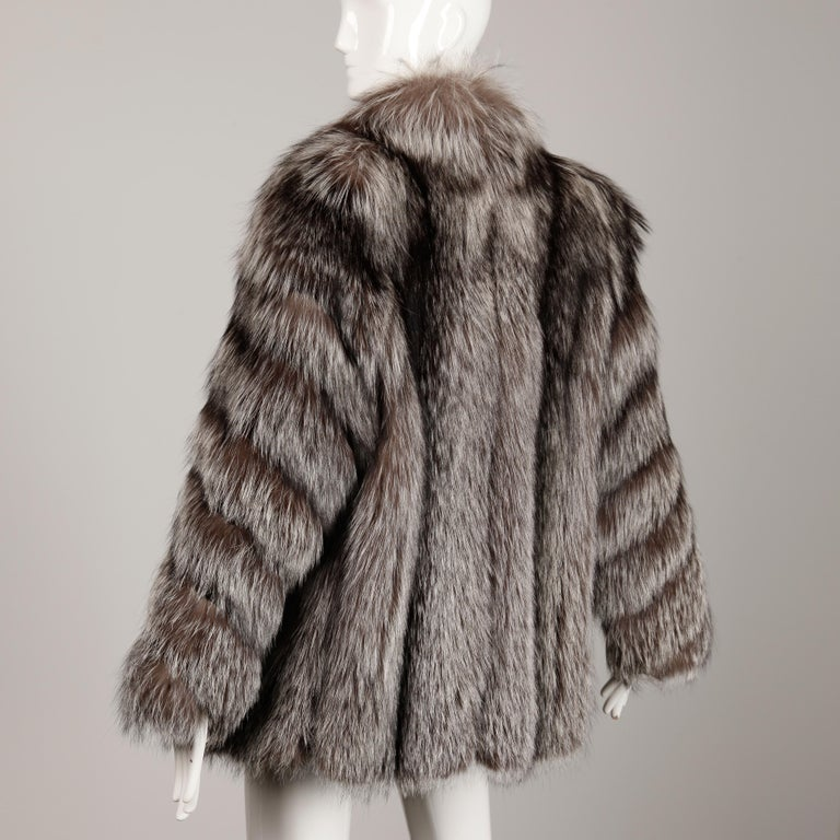 Absolutely stunning vintage chubby silver fox fur coat or jacket by Saga Furs. This coat is in beautiful condition with no shedding or drying to the pelts. It was always kept in cold storage and comes from a celebrity estate. It features velvet