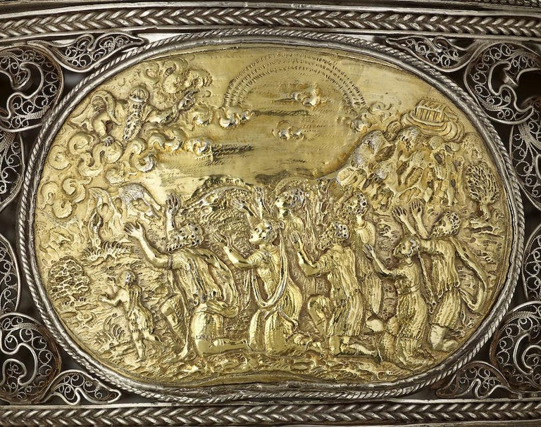 An extremely rare and unusual silver filigree toilet box, German, circa 1700, of circular design standing on three little bun feet; set within the box are four finely engraved silver gilt plaques of a much earlier date circa 1580 and probably