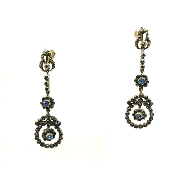 An unusual combination of delicate mid blue pastes and silvery marcasite make these pretty 1920s drop earrings distinctive and eye catching. Very much of their period and with a a 9ct screwback fitting, these earrings have a very finely decorated