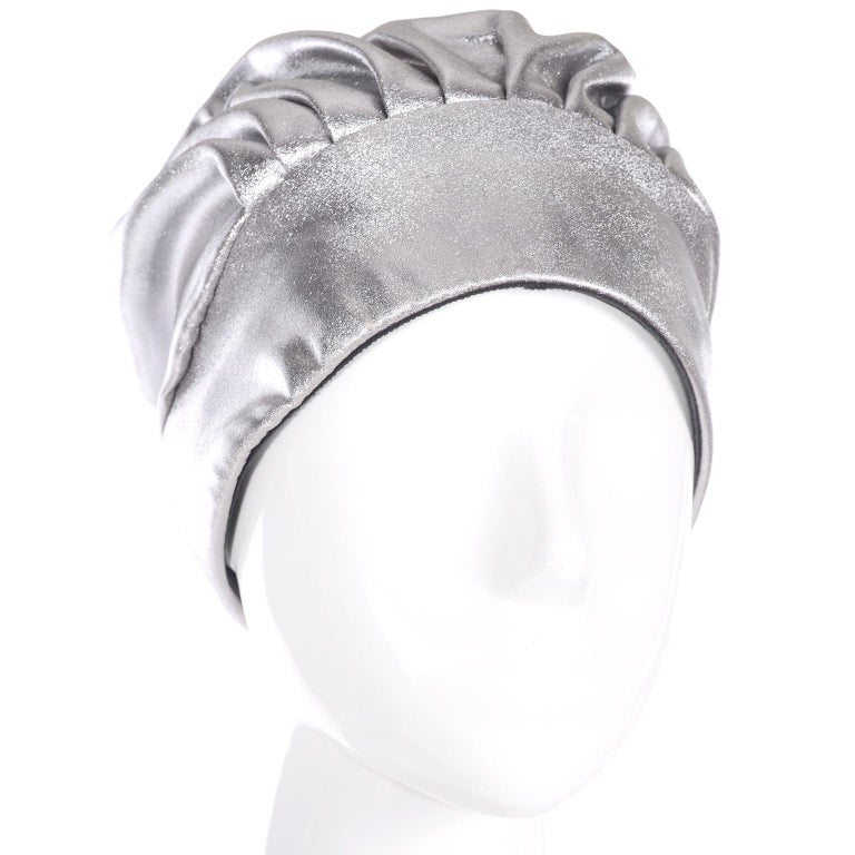This is a fabulous silver metallic hat with a bonnet or turban style. It is pleated in front and back, with a tie in the very back that hangs down. It is lined in black fabric. The hat has the Nicholas Ungar label from Portland, Oregon. Nicholas