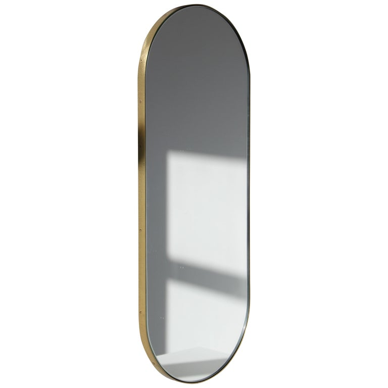 Silver Narrow Capsula Mirror with a Brass Frame For Sale