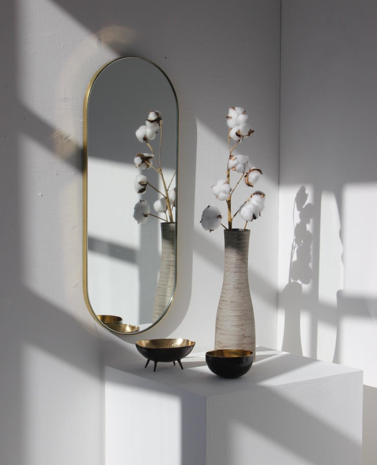 Delightful handcrafted silver capsule shape mirror with a brass frame.  Ideal above a console table in the hallway, above a beautiful fireplace, in the bedroom or in the bathroom.  Available with a bronze or black tint.  Measures: W 270 x H
