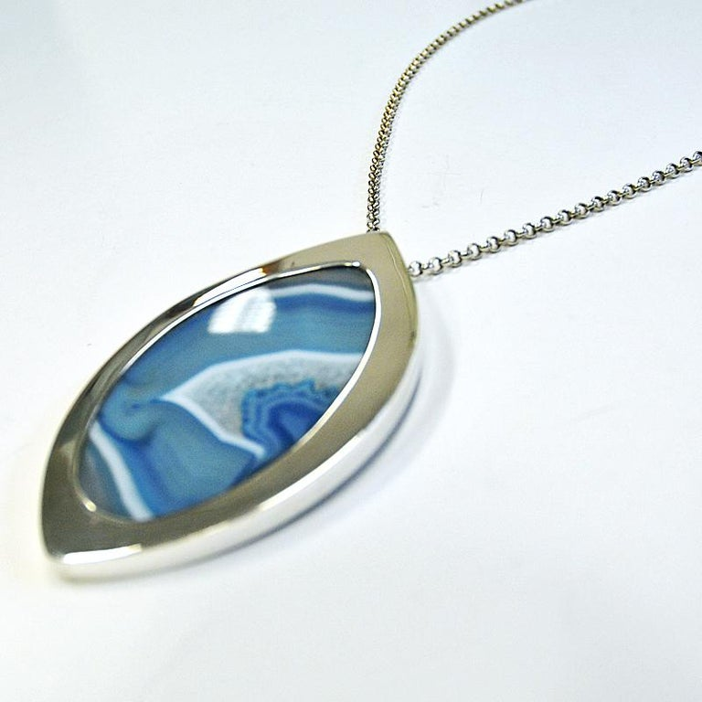 Stunning necklace by Marianne Berg for Uni Davidsen with a beautiful clear blue and white patterned agate stone surrounded by a polished silver frame. From the 1960s. The pendant is flat stone with amazing blue and white stone. Glazed and smooth