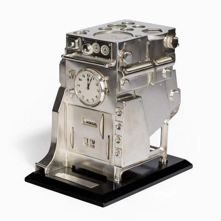 An unusual silver novelty perpetual desk calendar and clock, modeled as a ship's boiler, on an ebonized base with plaque inscribed:
