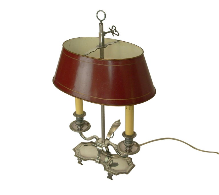 Silver plate Bouillotte table lamp with red tole painted shade. Holds two chandelier size light bulbs, recently re-wired, early 20th century.
