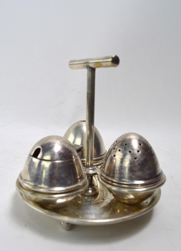 Silver plate condiment set made in England Aesthetic Movement design after Christopher Dresser. Silver plate finish shows minor wear, normal and consistent with age.