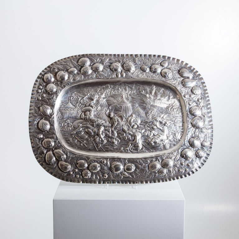 Oval silver plate with embossed nut and fruit decoration on the rim and detailed, dramatic battle scene in the mirror, probably depicting Samson slaying a Philistine.