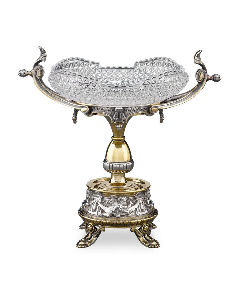This stunning pair of silver plate tazzas by Elkington and Co. exhibits a classical elegance. Greco-Roman style stands, which support cut-glass dishes, feature subtle gilding as a host of cupids populate the gallery at the base. Set on accented,