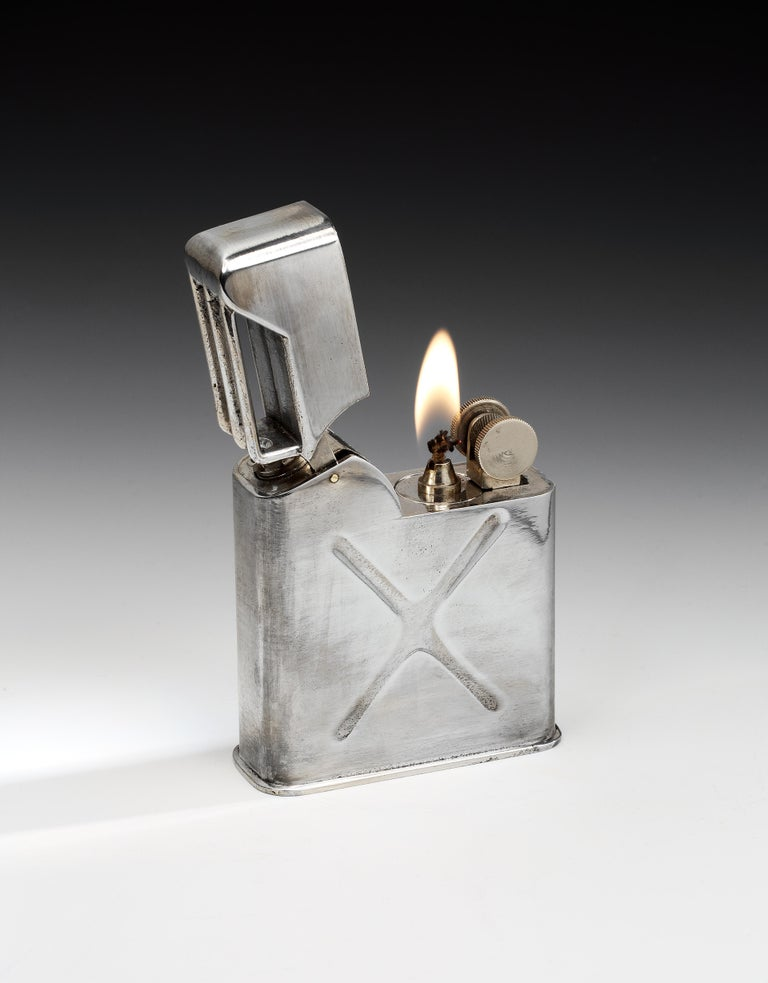 A very unusual 'military chic' novelty table lighter, known as the 'Jerrican', made to resemble a WW2 petrol can. This lighter features a heavy cast, silver-plated body with an aged patina, and an unusual double wheel mechanism, with flint wheel