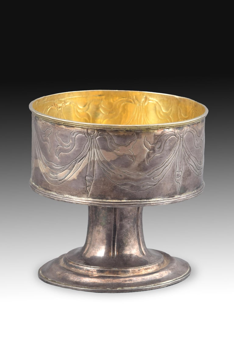 Piece made in silver (with the interior gilded) that shows a circular base elevated in two levels by smooth moldings and a grooved foot that leads into the container area, which is decorated on the outside with ribbons that hang from rings (this