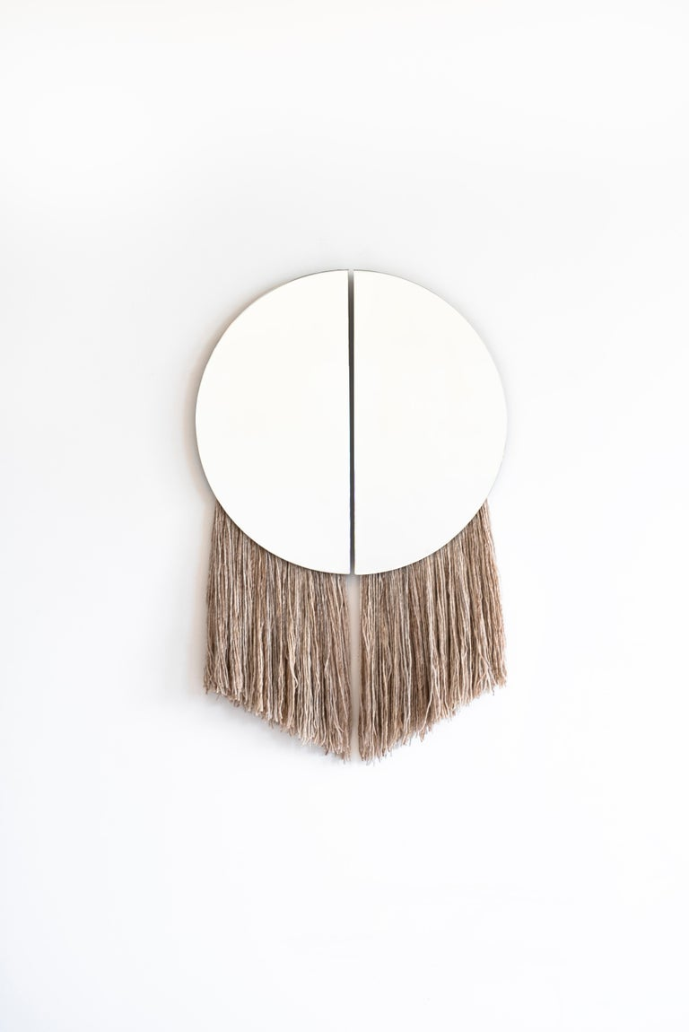 Named for the Greek God of the Sun, the Apollo Mirror is the marriage of sculptural and functional object, with two half circle mirrors joined by negative space and partnered with hand-spun, hand painted silk fiber.  Customization of mirror color,