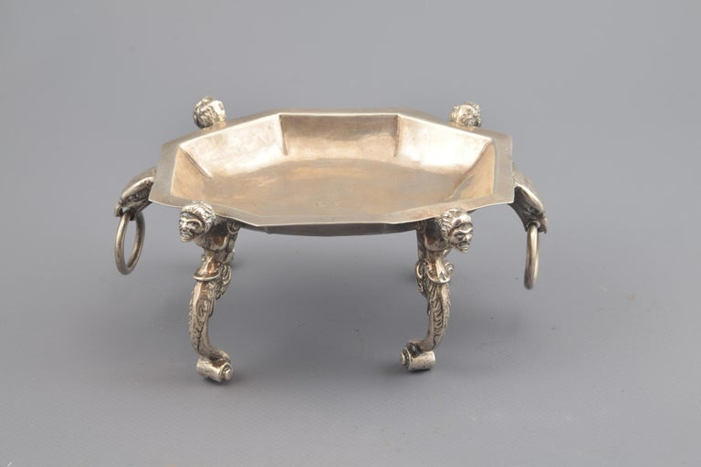 Specie or silver salt cellar in its color composed of a tray not very deep polygonal, raised and enhanced by four legs and also has two protomes of animals holding rings (eagles or lions). The legs have a lower scroll finish, which gives way to a