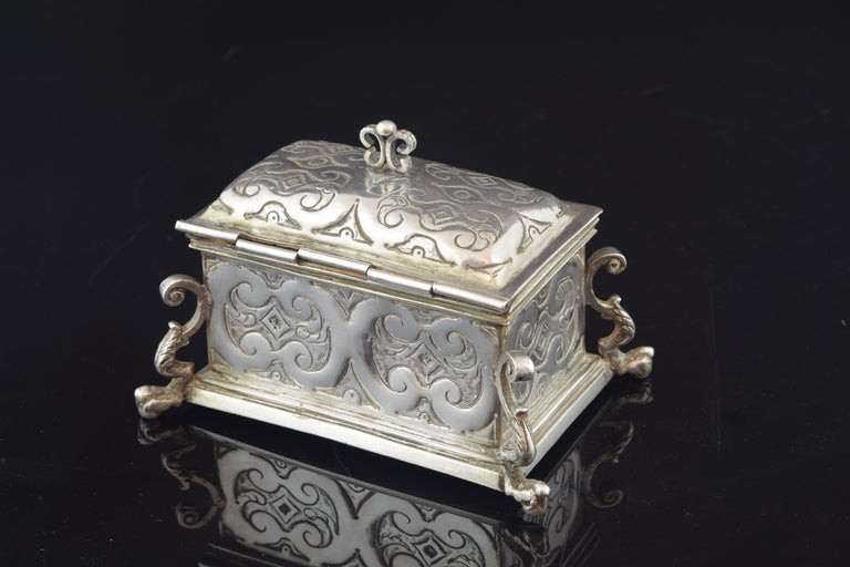The silver box has elaborate legs, fixed in the corners of the same, which are a combination of volutes in C, plant elements and a lower end reminiscent of a claw. The rectangular body has a decoration embossed in light relief based on ribbons in ce