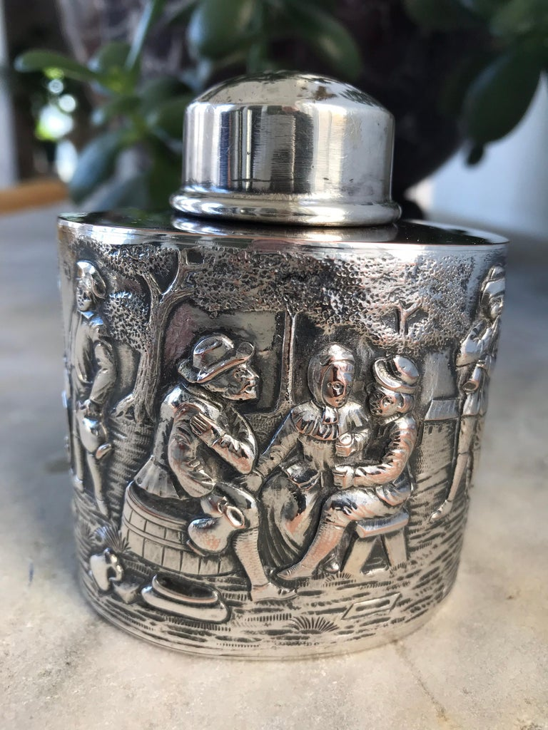 Antique silver plated tea caddy with high reliefs of a village scene surrounding the entire body of the tea caddy, illustrating musicians, dancers, taverner, a group socializing and drinking, and a very charming dog looking on. This quality caddy