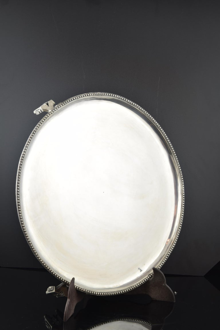 Silver salver Sola, Barcelona, 18th century.  Flat circular tray with slightly raised edge and decorated with a string of pearls raised on three legs formed by two rectangular recesses with moldings on balls flanking a floral motif. The contrast