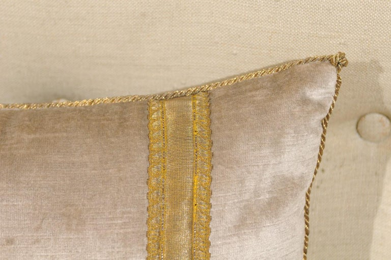 A rectangular silver velvet pillow adorned with European raised gold metallic embroidery depicting a lily flower. We currently have two pillows available, priced and sold individually. Featuring an exquisite décor presenting a European raised gold