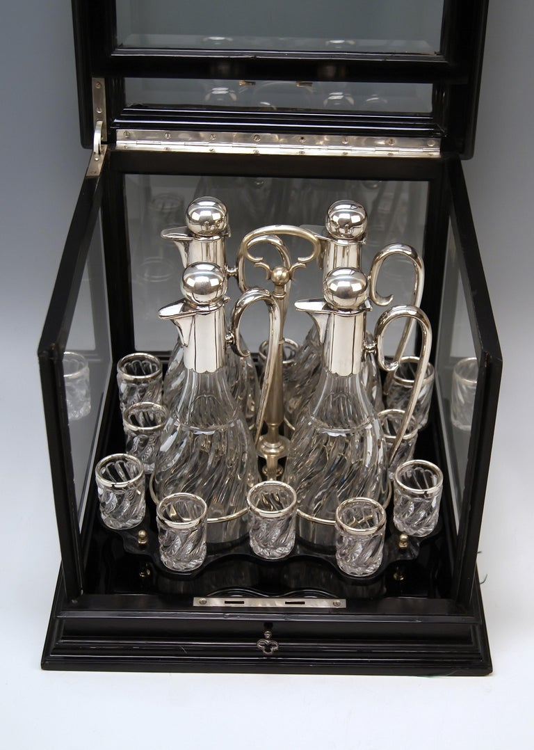 Silver Austrian gorgeous liqueur set of most elegant appearance.  Particular Feature: Set in original glass case! Elegant showcase / cabinet with black stained wooden frame. Glassed at five sides (= upper side is glassed, too !). Facet cut glass