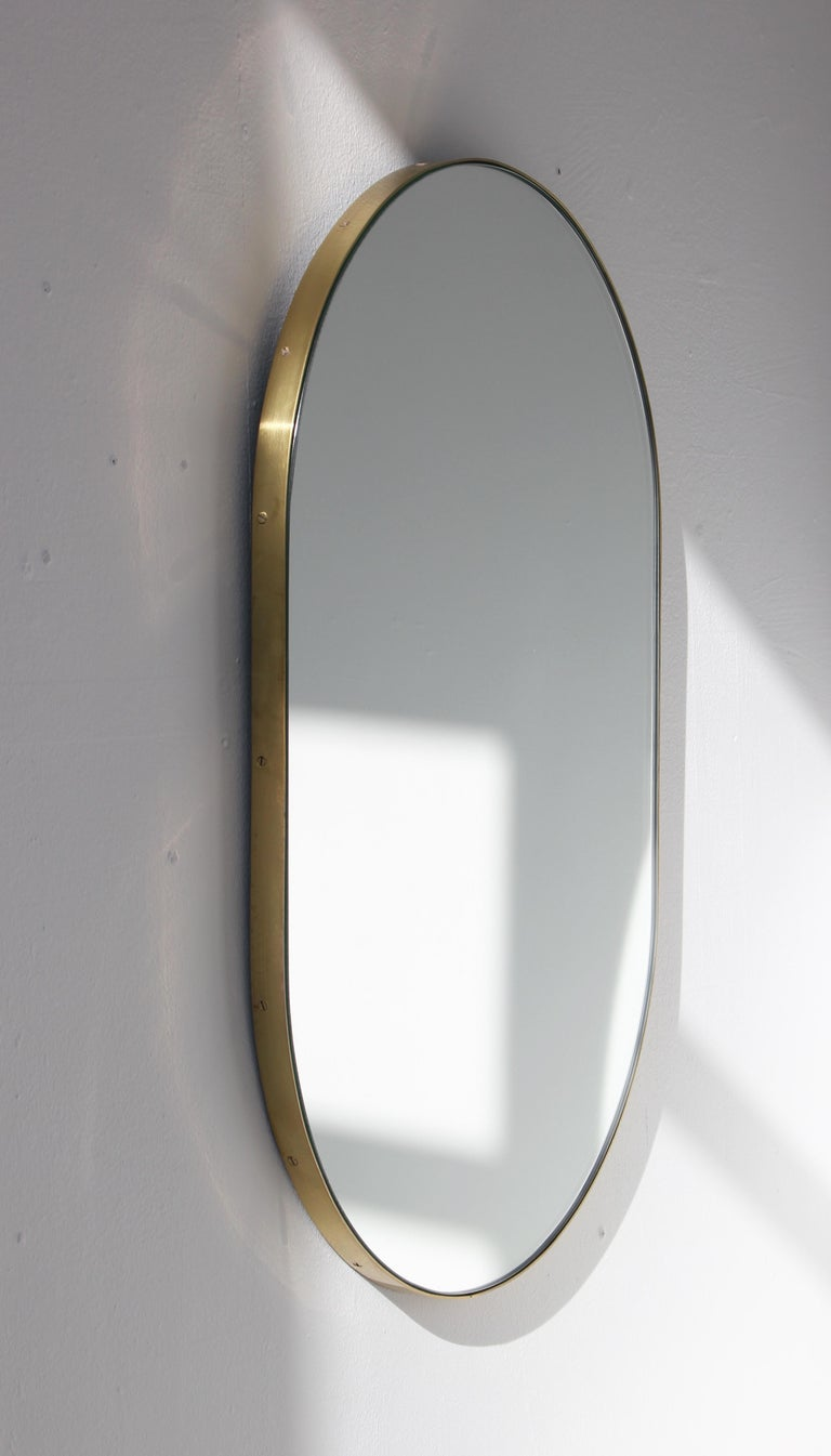 Delightful handcrafted silver capsule shaped mirror with a brass frame.  Ideal above a console table in the hallway, above a beautiful fireplace, in the bedroom or in the bathroom.  Available with a bronze or black tint.  Measures: W 370 x H