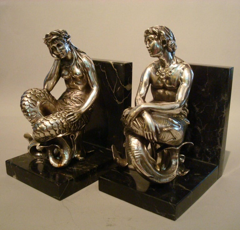 Silvered bronze bookends sculptures of a Mermaid and Merman, France, 1900. This enchanting bronze sculpture is the object of many sailors dreams. Silvered bronze sculptures of a mermaid and merman. A female figure, nude from the waist up, boasts a