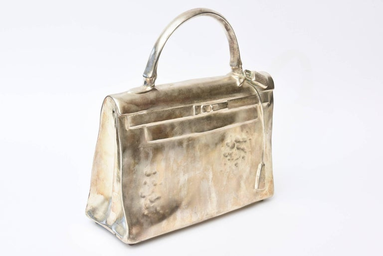 This amazing sculpture by the well known French artist and sculptor, Christian Maas is a silvered bronze life-size rendering of the infamous Hermes Kelly Birkin bag. It was a limited edition of 100. It was done in 1990. It is titled the