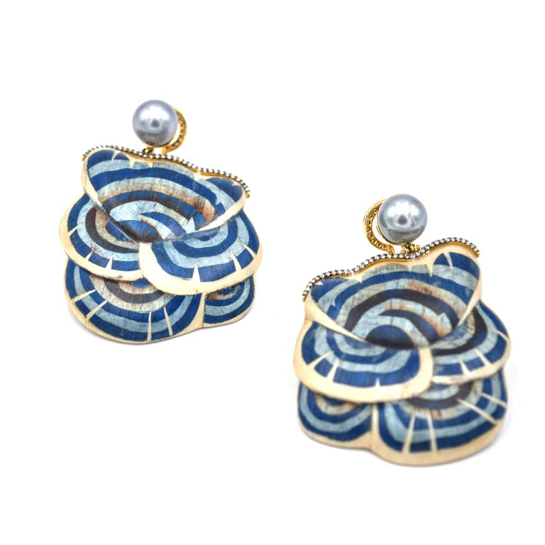 Exposing the rich colors and patterns embedded within cultures all around the world, Silvia Furmanovich designs distinctive jewelry inspired by nature and ancestry.  These blue mushroom marquetry earrings feature grey pearls and light brown