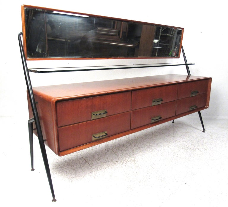 Silvio Cavatorta mahogany cabinet with six drawers, horizontal tilting mirror, and glass shelf with brass trim.