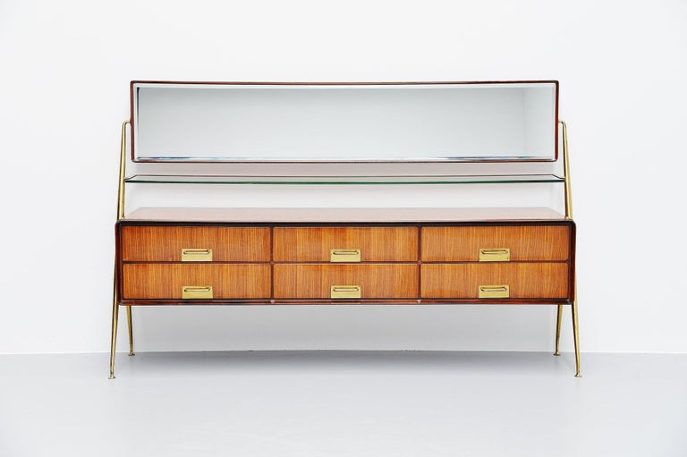 Stunning mirror sideboard designed and manufactured by Silvio Cavatorta, Italy, 1958. This highly refined sideboard has a brass structure, the cabinet is made of high gloss lacquered teak with nice grain to the wood and the 6 drawers have brass
