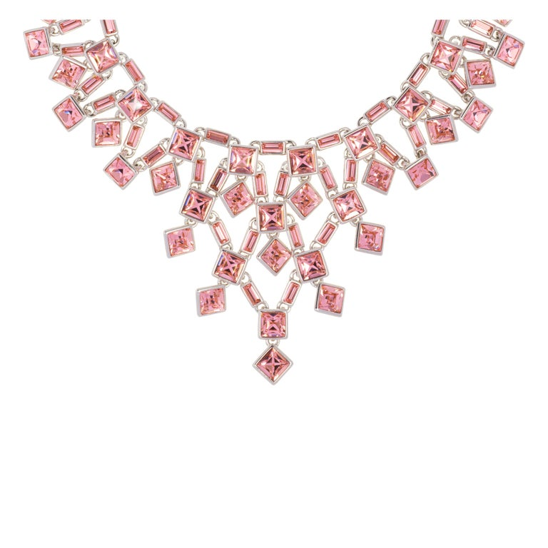 The Claudette Crystal Necklace flows elegantly around the neckline. The square Swarovski® crystals catch the light and the subtle changing tones of the crystals constantly sparkle. The Necklace makes a bold statement of high glamour.  The Claudette