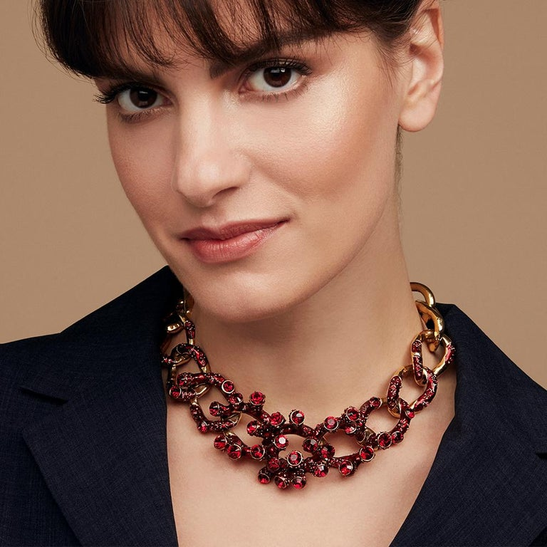 An opulent necklace that swathes the neckline in crystal coral forms. A highly crafted piece, each link evolves with added detail and texture towards its sculptural centre piece. The links of the necklace graduate from smooth at the back to become