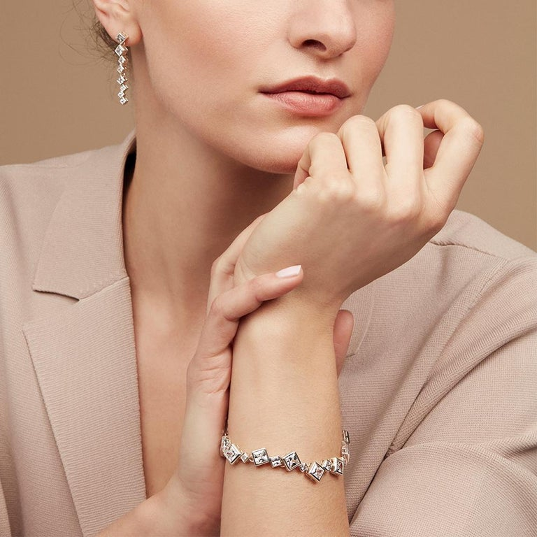 The Icicle bracelet is formed from a sequence of square cut cubic zirconia stones seamlessly interlinked at off-set angles following the natural flow of crystal formations. The fastener is a cleverly constructed rocker-clasp, concealed and secure,