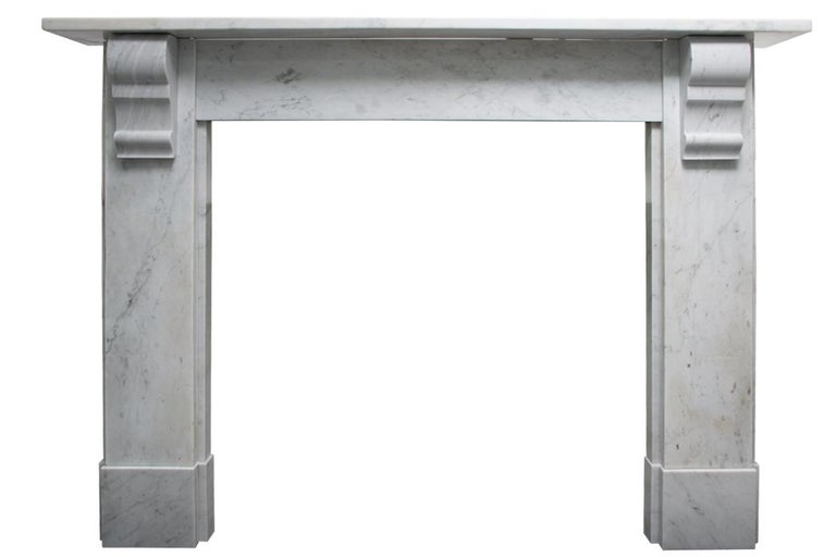 Reclaimed Victorian Carrara marble fireplace surround with simple geometric corbels supporting the shelf, circa 1880.   Pictured with an original cast iron and tiled grates, sold separately.
