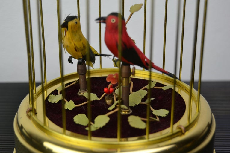 Mechanical birdcage with two singing birds inside. This automaton has a red and yellow singing bird in the cage.  As well the birds as the plants are very fine detailed.   The birds in this singing bird music box have realistic sound of real