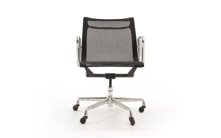 Newer production Charles and Ray Eames for Herman Miller Aluminum Group armchair in black mesh upholstery with casters. Five prong base. Very good condition. Ready to use.