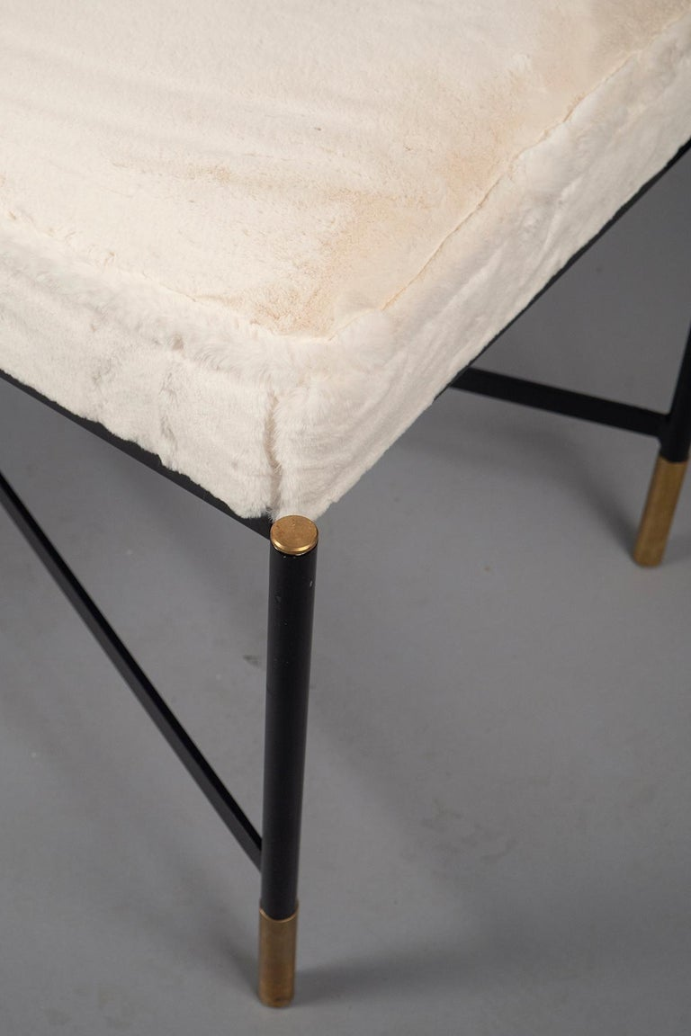 Black painted bench featuring a X-stretchers and brass sabots and caps. Upholstered in extremely soft faux sheepskin.