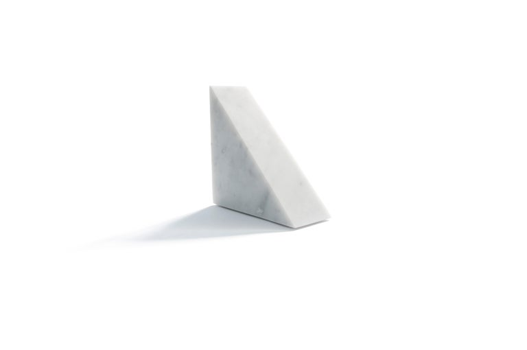 Single big bookend or decorative object in white Carrara marble with triangular shape. Each piece is in a way unique (every marble block is different in veins and shades) and handmade by Italian artisans specialized over generations in processing