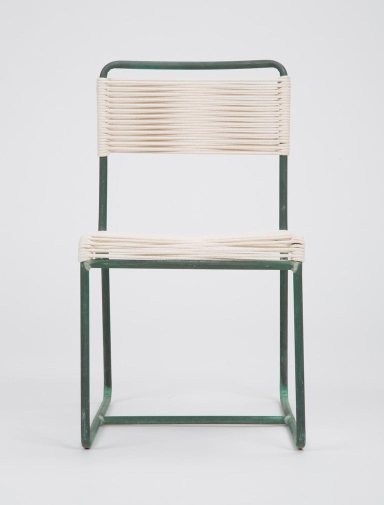 A model C1700 patio dining side chair in patinated bronze, designed by Walter Lamb and produced by Brown Jordan. The chair has a tubular frame supported by a bent bronze runner, terminating in a decorative curl just below the seat. The frame is