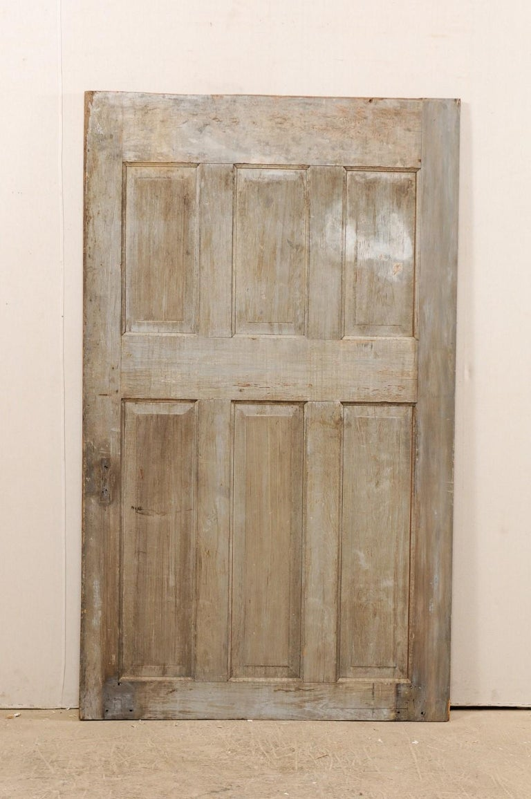 A single European 19th century six-panel wood door. This antique door with nicely-sized width features six raised panels at both front and back sides. Each door has three shorter vertically positioned rectangular-shaped panels sitting directly about