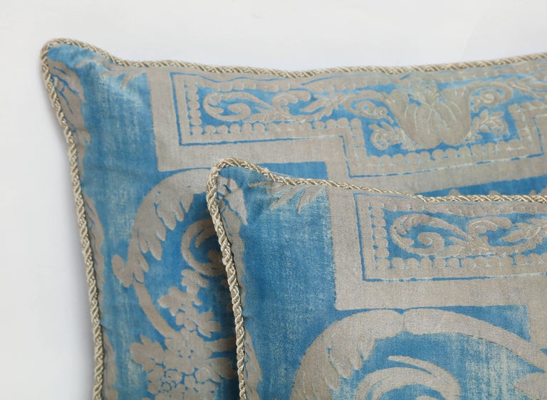 A Fortuny silk pillow cushion in metallic blue and silver fabric depicting a neoclassical design with a draped garland motif, with braided trim and woven back.