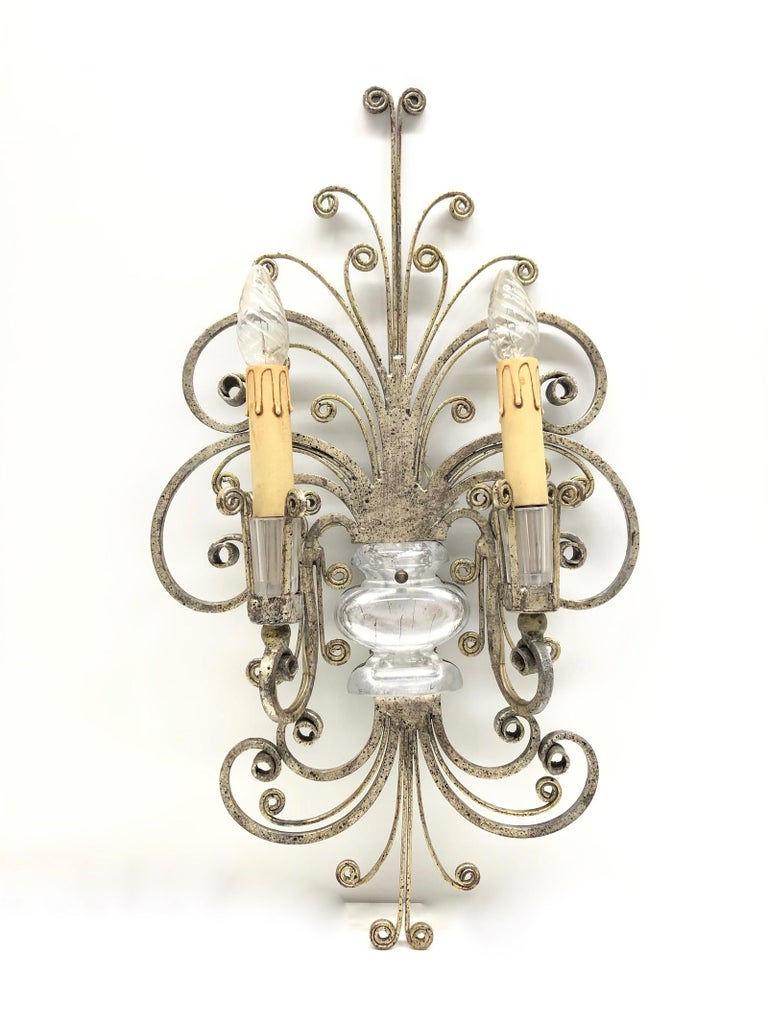 A single silver tone iron floral sconces of Maison Baguès with crystal urn motif, socket cover also made of crystal glass. The fixture requires two European E14 candelabra bulbs, each bulb up to 40 watts. The wall light has a beautiful patina and