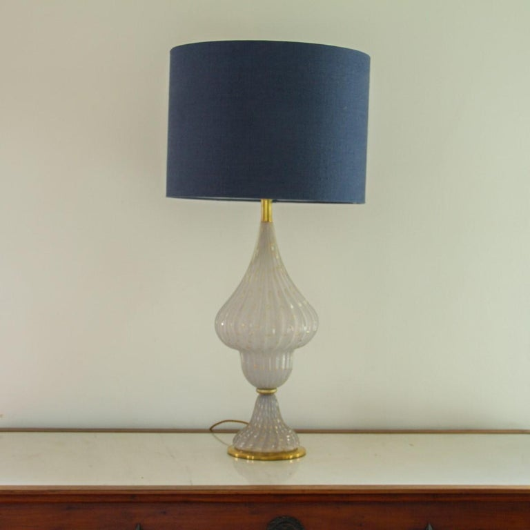 A single psykter shaped lamp made from Murano white glass which has been ribbed and blown with gold bubble details throughout. The lamp is set on a brass base and has brass details accentuating the shape,1960s. We also have a pair of matching