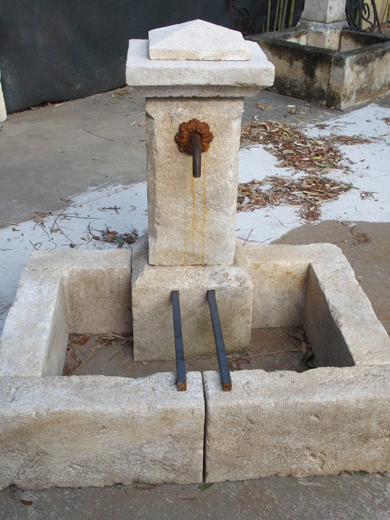 This hand carved and distressed limestone fountain from Provence can be used as a wall fountain or placed in front of shrubbery, gates or other edifices. The top of the fountain is stepped out with a shaped piece on top. A single squared pillar is
