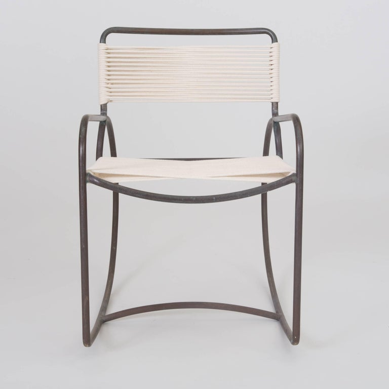 A single bronze rocking chair designed by Walter Lamb and produced by Brown Jordan. The chair has a sculptural shape, with a single formation of tubular bronze forming the backrest, arms, and exaggerated round runners, and terminating in a stylistic