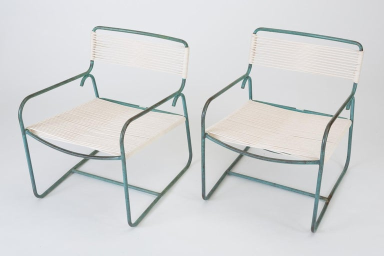 A wide patio lounge chair by Walter Lamb for Brown Jordan. The chair has a simple construction in tubular bronze with a patinated finish, with rounded squares serving as runners on each side. The backrest, and seat are both woven in cotton sail