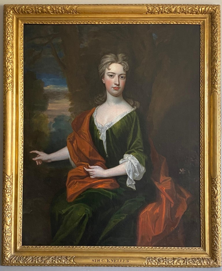 An extremely rare signed portrait of a Lady by Sir Godfrey Kneller. The lady, three-quarter length, seated in a landscape, wearing a green silk gown with red cloak, gesturing  to her right. Oil on canvas in the original 18th century giltwood frame.