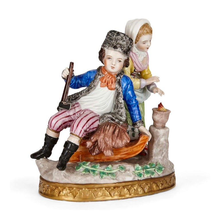 Sitzendorf porcelain group of a young couple German, c. 1900 Measures: Height 16cm, width 14cm, depth 9cm  This charming and vibrantly coloured porcelain group depicts two figures—one a young boy, the other a young girl—in warm winter dress. The